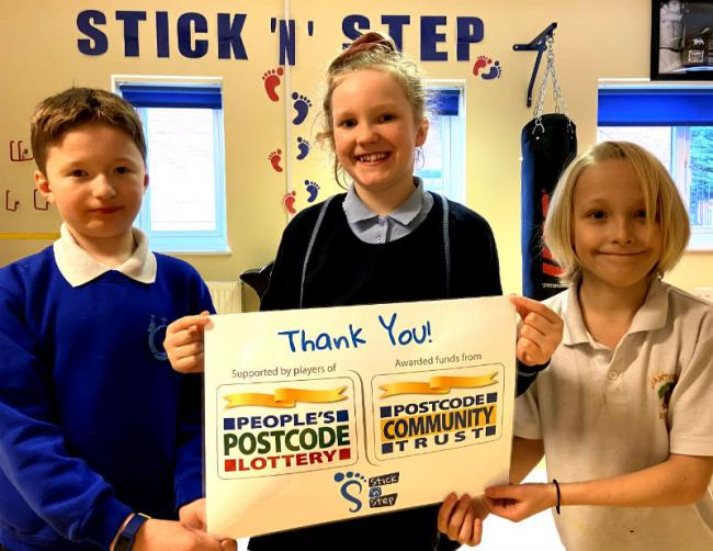 Children who attend conductive education classes at the Stickn'n'Step's centres in Runcorn and Wallasey with the cheque from People's Postcode Lottery