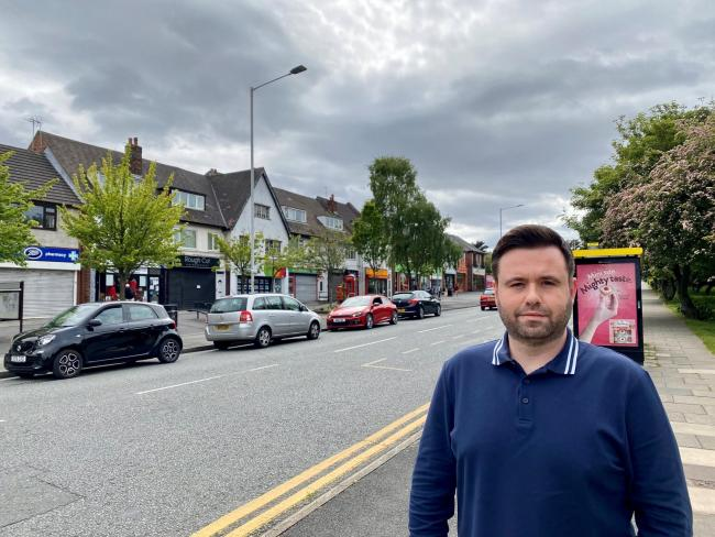 Councillor Tom Anderson stood outside shops in Greasby that could benefit from the extra cash
