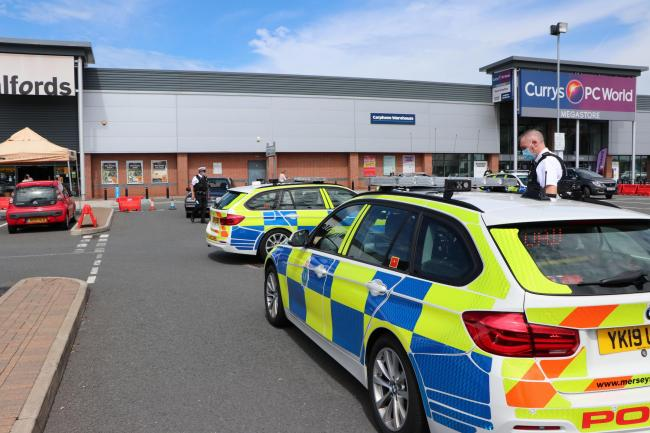 Police at the scene of the incident at the Croft Retail Park in Bromborough. Photo: Richard Garnett