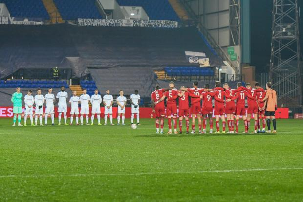 Wirral Globe: Players observe a minutes' silence in memory of world football great Diego Maradona. Photo: Phil Bryan