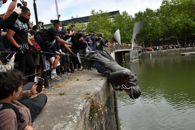 The statue of slave trader Edward Colston is dumped into Bristol harbour during a Black Lives Matter protest. Photo: PA