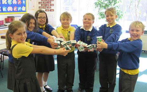 Pupils from Brookdale Primary School with yogurt pots they have saved from landfill.