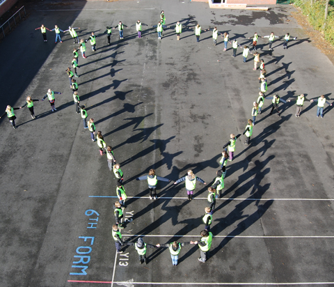 Pupils from Black Horse Hill Junior wear hi-vis jackets and positioned to form an image of a light bulb, an idea thought up by the Hilbre High Humanities College students.