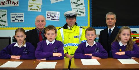 Cllr Harry Smith, Sgt Paul Mountford and Mr Kennedy, Headteacher of Black Horse Hill Junior School with the four pupils who presided over the Kids Court.