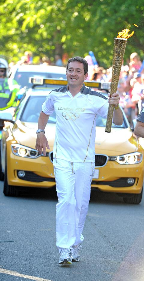 Chris Boardman carries the Olympic Torch in Birkenhead Park last year. Picture: Paul Heaps
