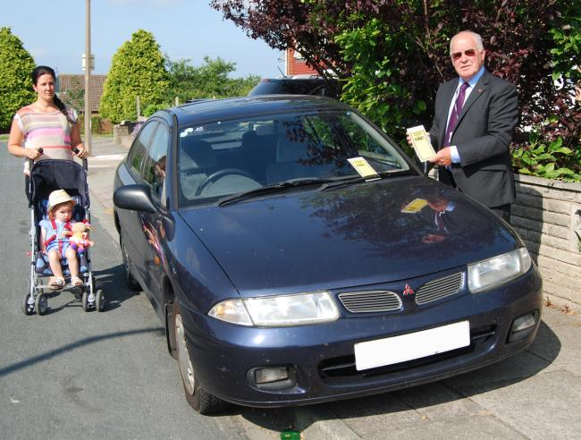 Cllr Harry Smith 'ticketing' a car which is obstructing the pavement, forcing a young mum to push her buggy and child into the road.