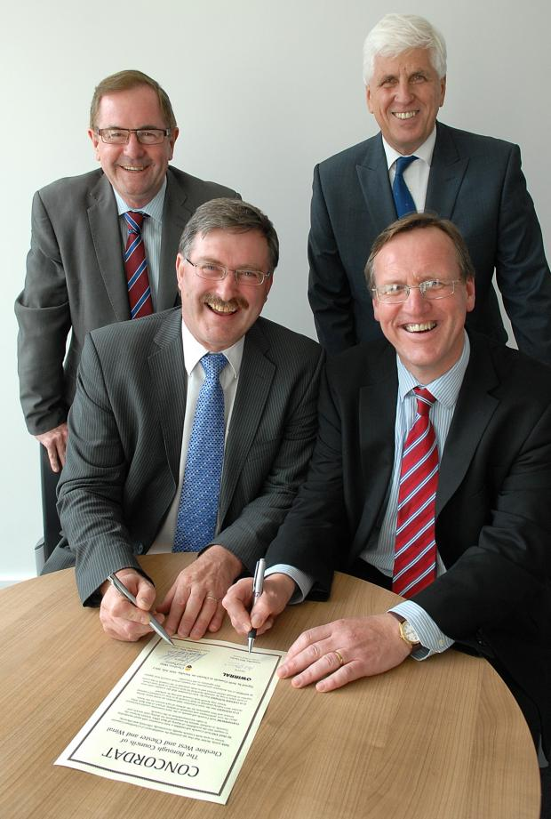Wirral Globe: FLASHBACK: Councillors Mike Jones and Phil Davies signing the 'Concordat' to share services watched by chief executives Steve Robinson and Graham Burgess