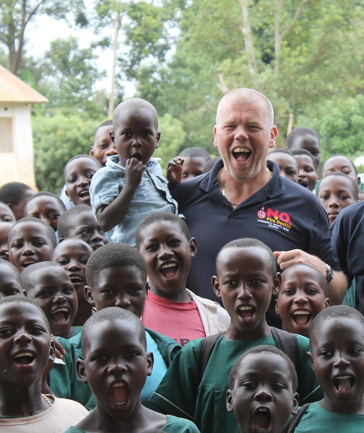 Watch Manager Phil Hunt with pupils who were taught about fire safety during his trip to Uganda.