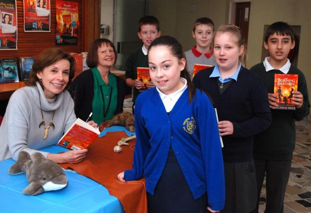 Pupils meet author Michelle Paver, while children's librarian Sue Roe looks on.