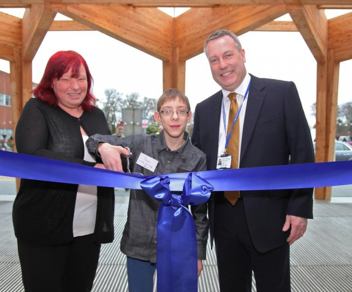 Joshua Welch cuts the ribbon with his mum Erica and chief executive David Allison.