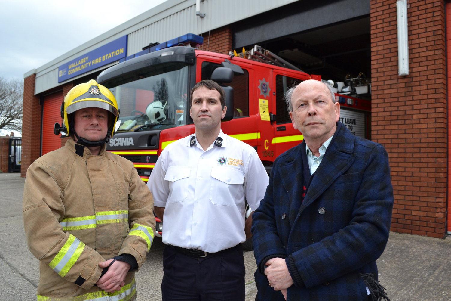 Group manager Paul Murphy (centre) pi0ctured with an MFRS firefighter and Terry Sullivan from Wirral Older People's Parliament during Home Safety Month. Photo by Merseyside Fire & Rescue Service.