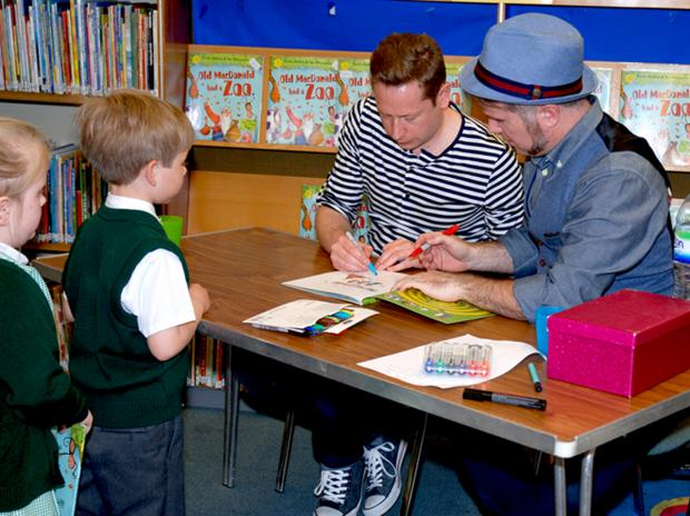 Curtis and Tom sign copies of their books at Bebington Children's library
