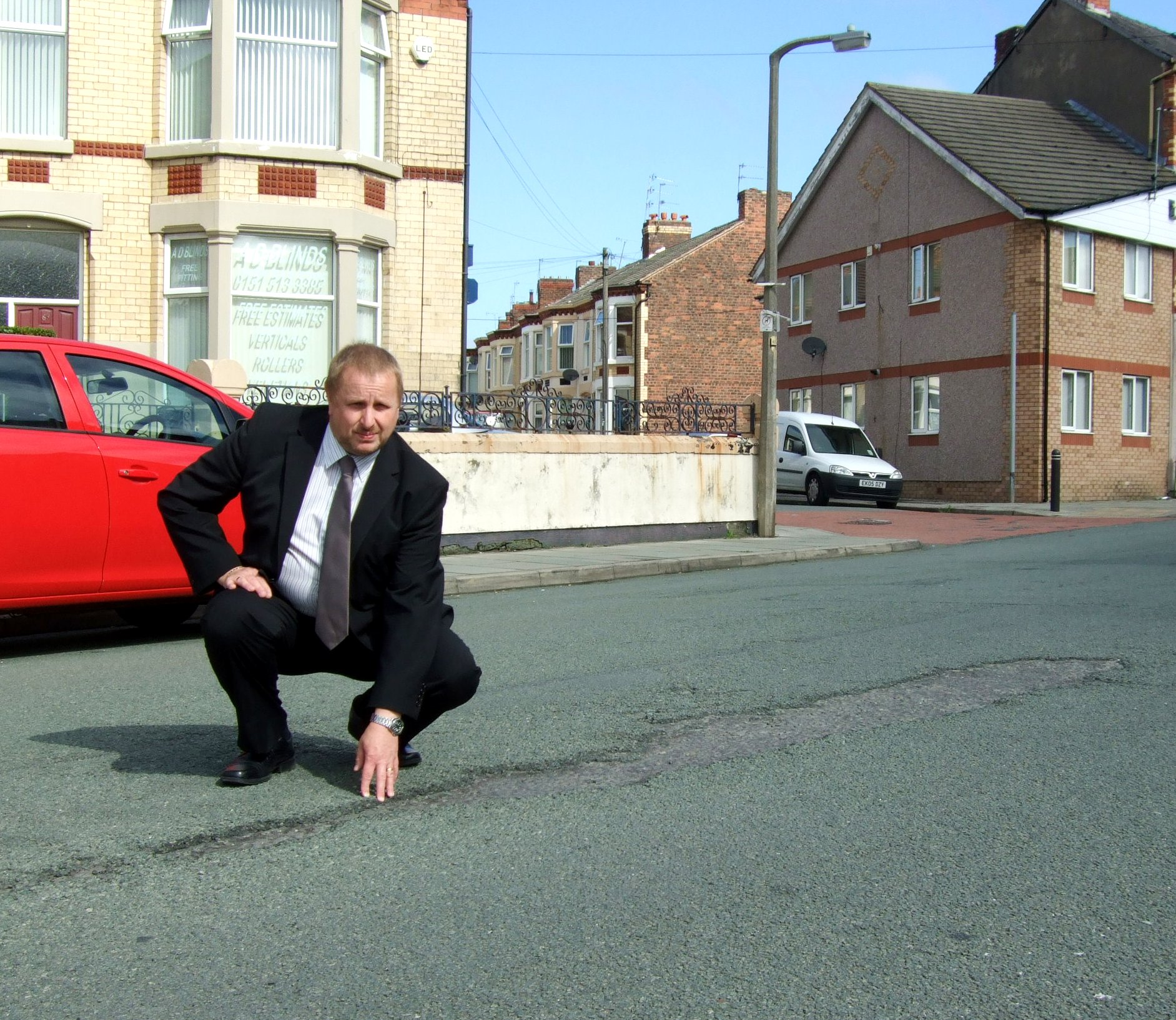 Cllr Stuart Whittingham checking out some of the potholes on Martins Lane, Liscard, which will be repaired soon thanks for the additional funding.