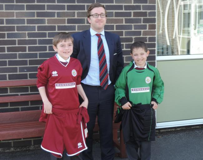 Kevin Donoghue, Solicitor Director of Donoghue Solicitors, presents the football kits to Frankie Spargo and Callum Maitra, students of Orrets Meadow School.