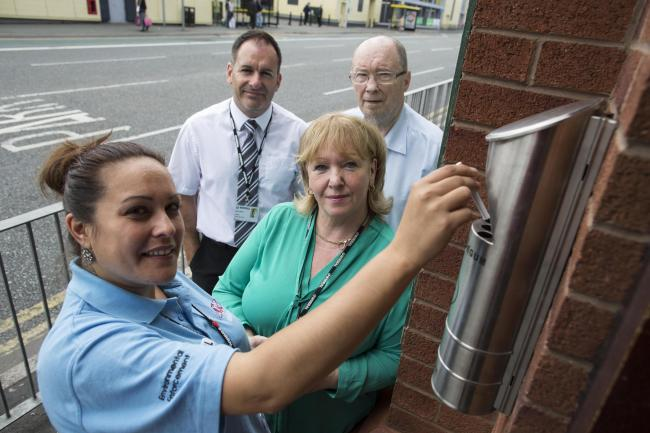 Jackie Kavanagh, from Kingdom, shows Cllr Bernie Mooney how cigarettes should be extinguished using a wall-mounted cigarette bin situated outside The Mackenzie in Birkenhead. Also pictured are Steve Smith, from Kingdom, and Paddy Downey, pub manager