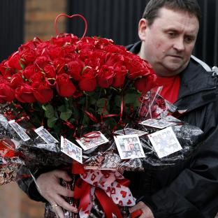 Wirral Globe: Roses are carried to be placed at the Hillsborough memorial plaque during the Hillsborough 27th Anniversary Memorial Service at Anfield