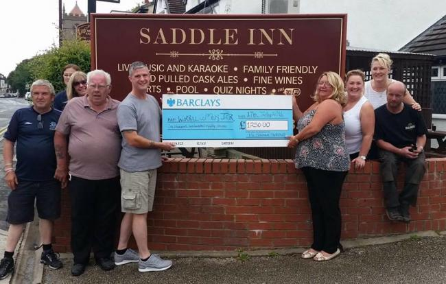 Landlady Lynn Anderson (right) presents the cheque to Wirral Copper Jar member Mark Witty