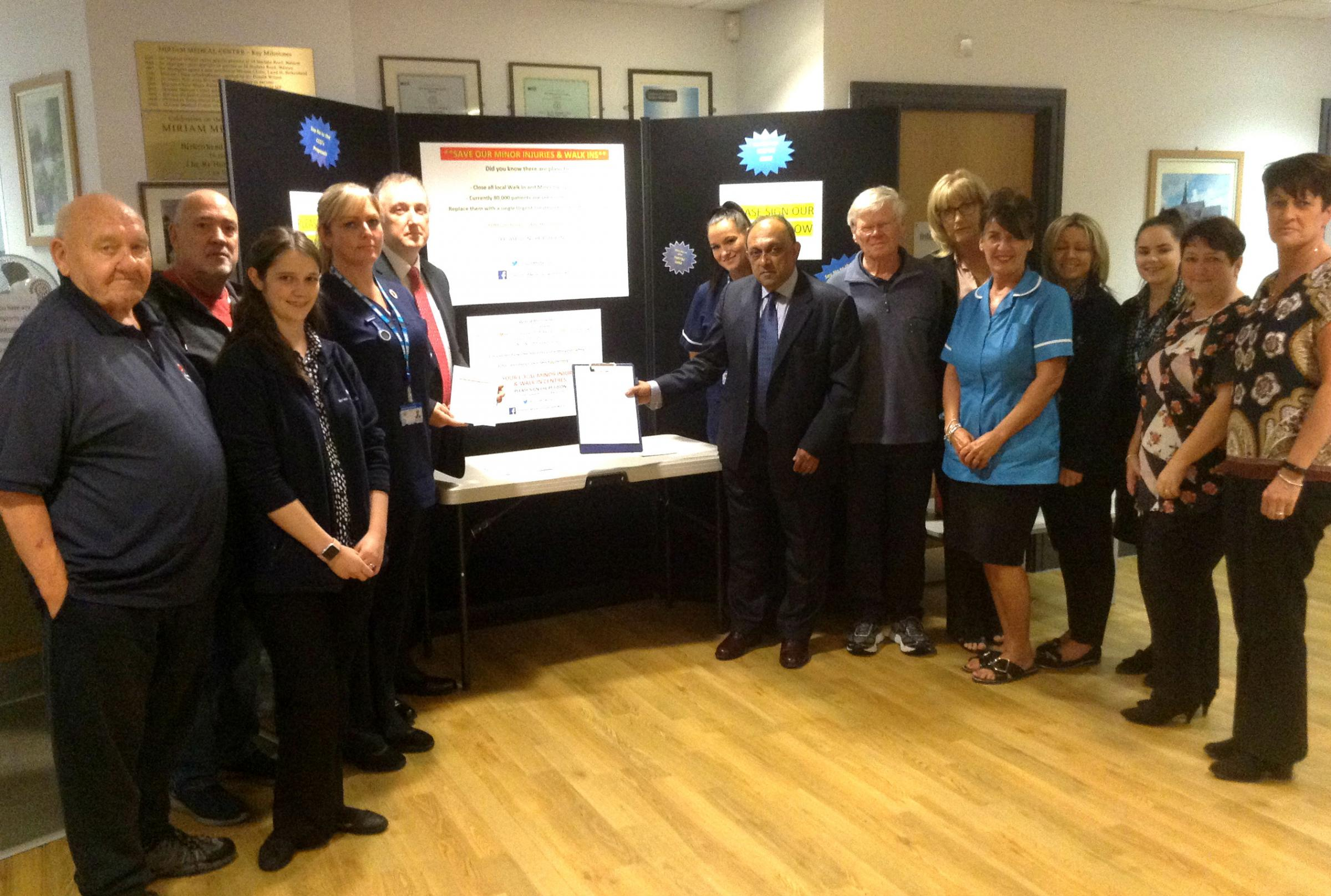 Dr Abhi Mantgani - senior executive partner at Miriam Medical Centre in Birkenhead's Laird Street - pictured with petition and members of staff and patients' group