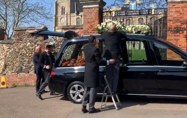 Wirral Globe: Flowers being placed in and on the hearse