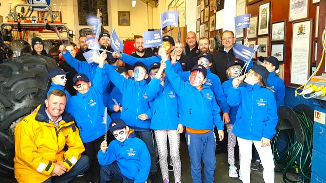 The children showcase their goody bag gifts as they line up with RNLI lifeboat crew (RNLI/Cherie Rowlands)